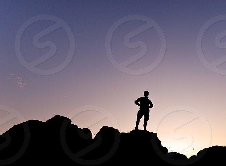 Man s silhouette in the high of a hill at the sunset - Horizontal photo