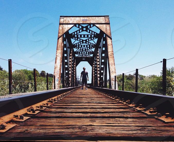 person standing on gray and brown bridge photo