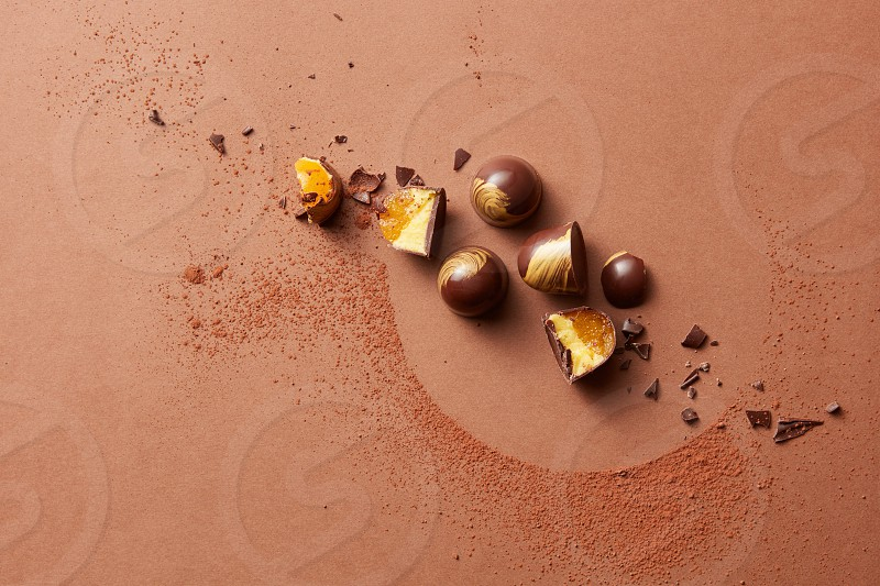 broken chocolate candies with jelly on a brown background photo