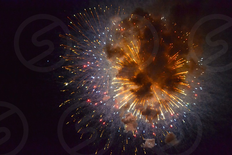 orange red and white fireworks in smoky night sky photo