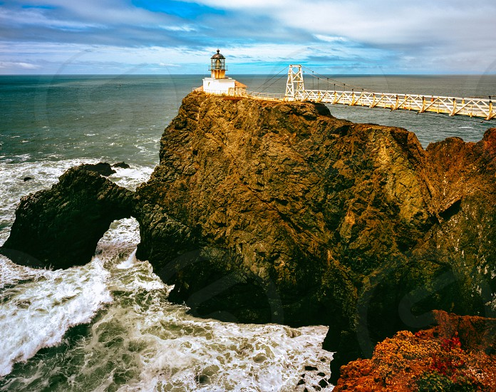 light house and rock formation photography photo