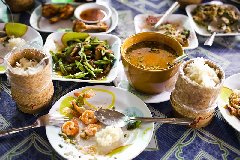 Comfort food Thai dishes for sharing on the table spicy soup prawns curry vegetables and sticky rice photo