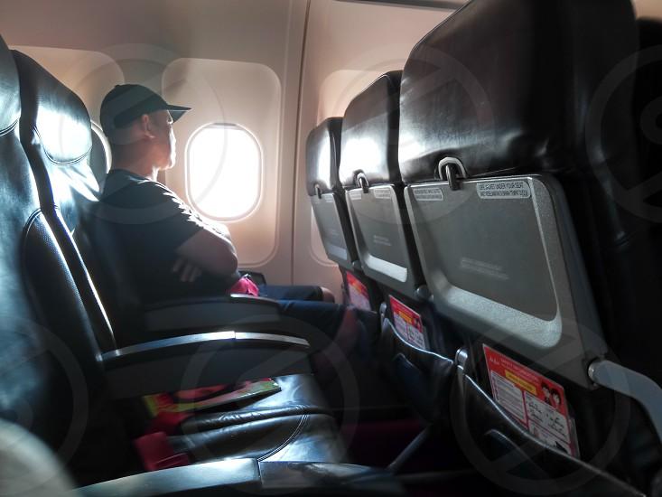 photo of a man sitting beside airplane window photo
