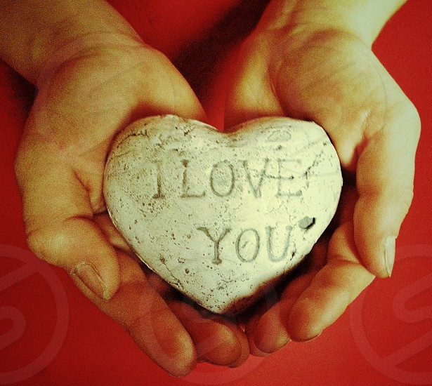 hands holding stone that says i love you photo