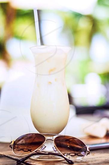 aviator sunglasses near glass of drink photo