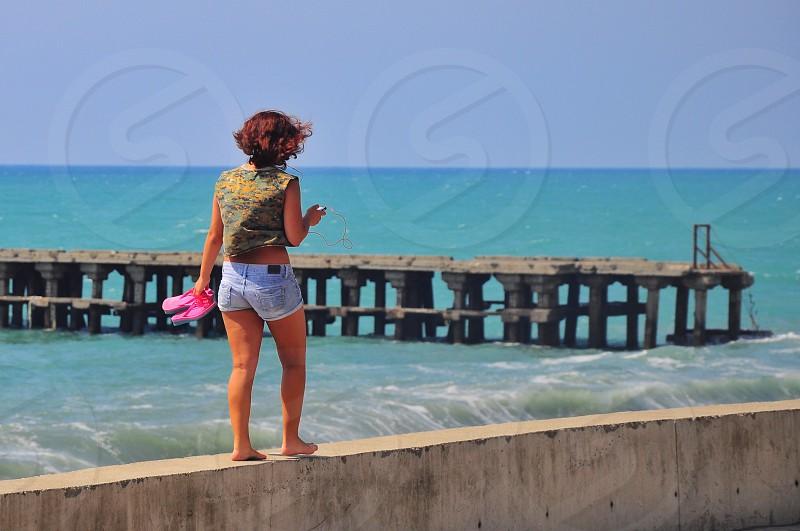 woman walking on sea wall photo