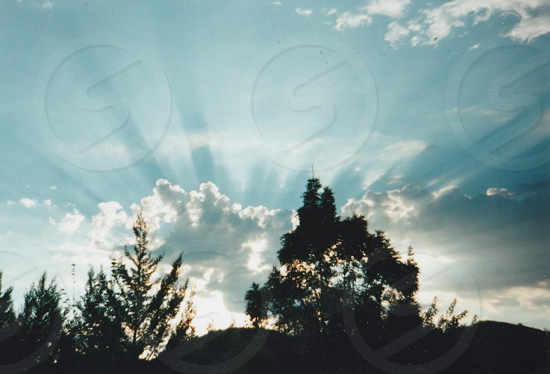 Sun setting with sunrays shining behind the clouds  photo