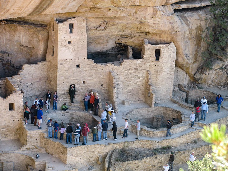 Visitors to popular Mesa Verde National Park in Colorado USA listen as a Ranger leads a tour of the ancient pueblo cliff dwelling ruin Cliff Palace. photo