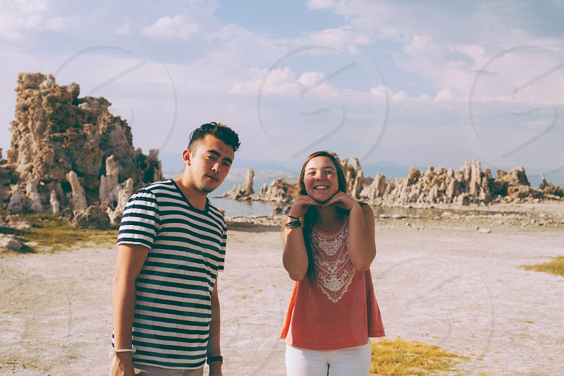 man in white and black stripe crew neck t shirt beside woman in pink white heart t shirt under white cloudy blue sky during daytime photo