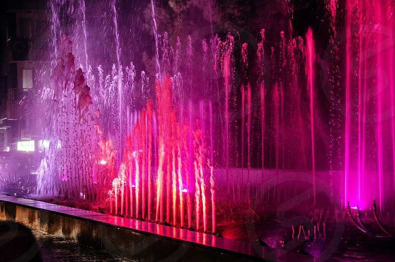 A pink water fountain at night. photo