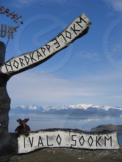white and black nordkapp elokm ivalo 500 km sign with brown moose plush toy photo