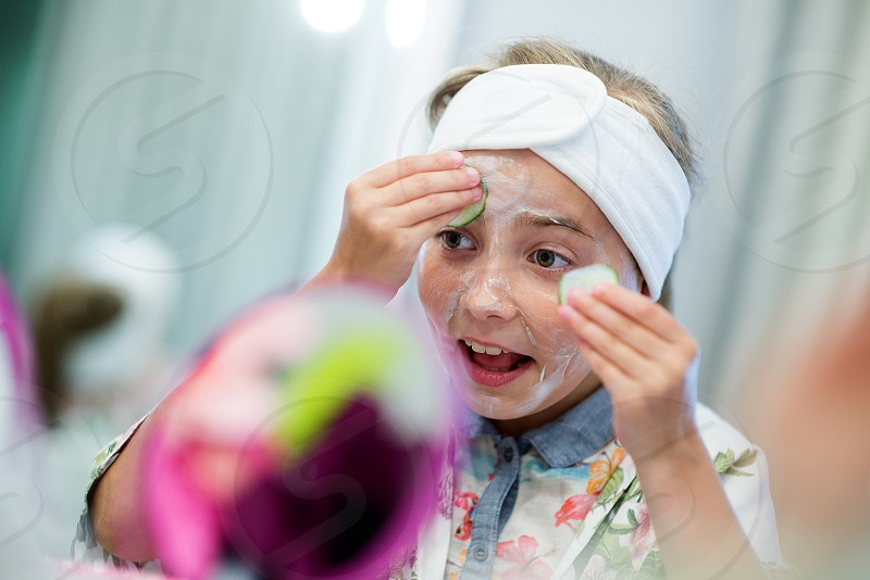Girls enjoying the excitement of a birthday party at a children's spa. Here for the first time they encounter the facial procedures skills like skin care and applying masks. Fun educational and relaxing activity for little princesses.  photo