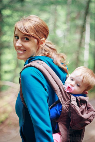 woman in blue hoodie smiling and carrying boy photo