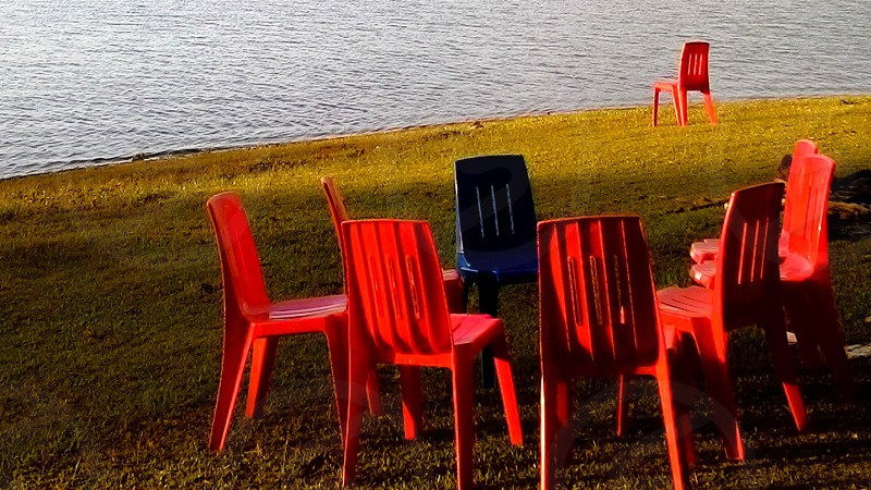 lone chair beyond a circle of chairs besides a beautiful view of a lake photo