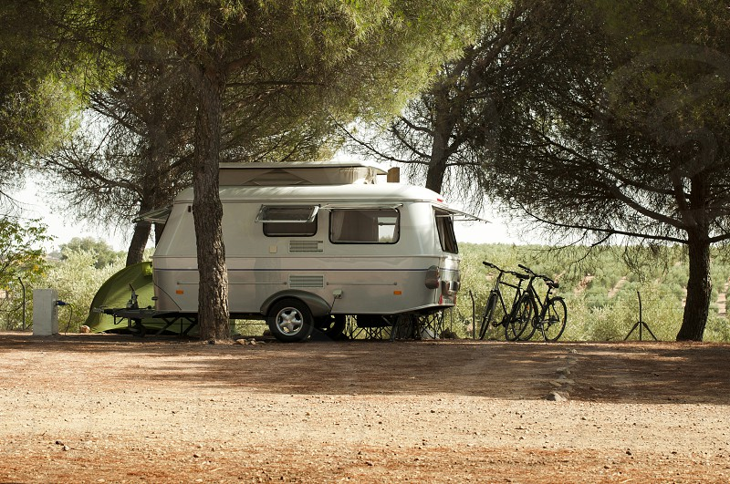 Small white caravan through the trees. Green tent and bikes. photo