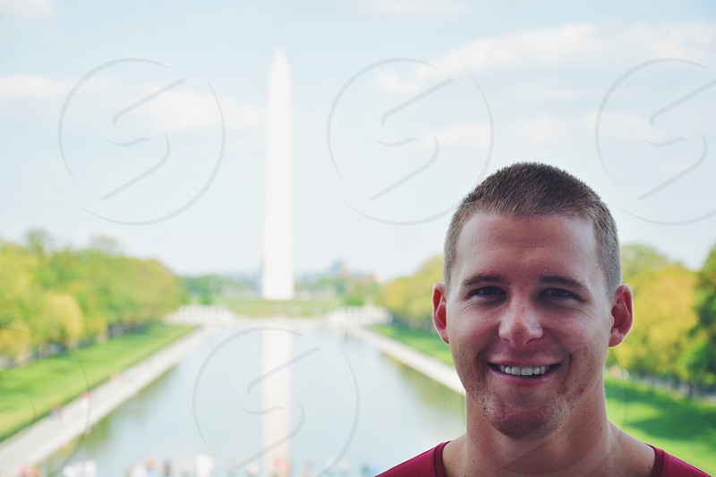 man wearing red top standing at the back of Washington Monument photo