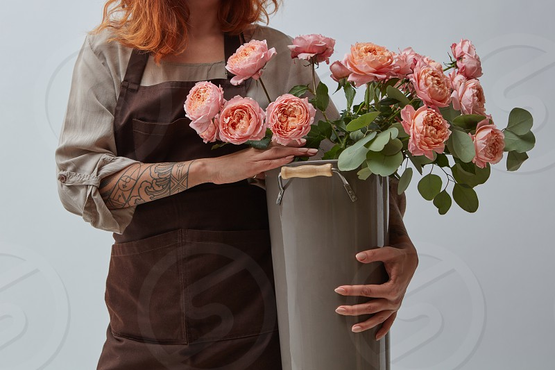 A woman with a tattoo is holding a big vase with pink media roses. Mothers Day. Flowers shop concept photo