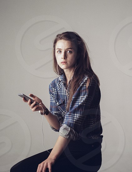 woman in blue white and grey plaid dress shirt and black pants sitting and holding silver iphone 6 photo