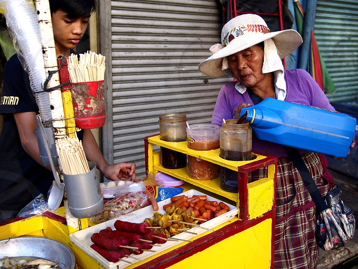 ANTIPOLO CITY PHILIPPINES - OCTOBER 31 2018: A street vendor sells assorted fried food on her food cart at a sidewalk. photo
