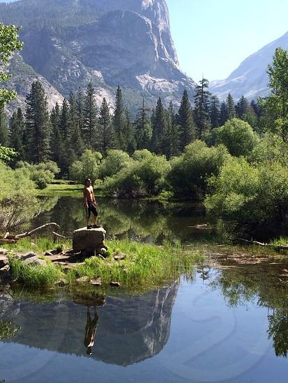 photo of man in black shorts standing on grey rocks facing green trees photo taken during daytime photo