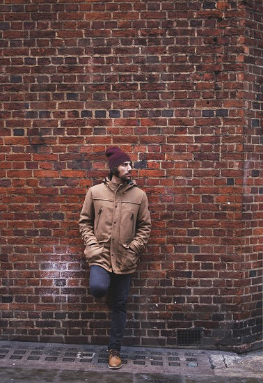 young man with duffle coat on a brick wall London photo