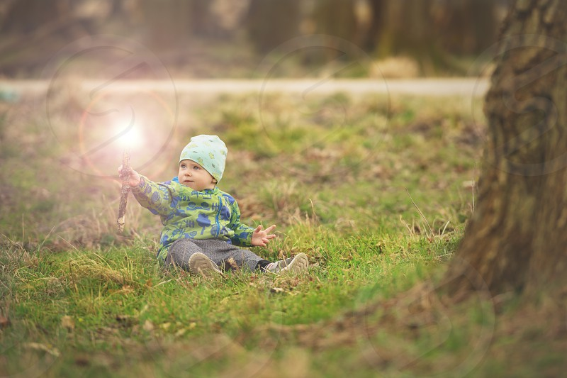 Small boy is sitting on grass and handling magic wand in spring park near big tree photo