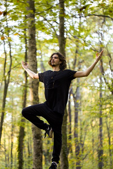 A young man stands on a moss-covered rock in a beech forest and doing yoga photo
