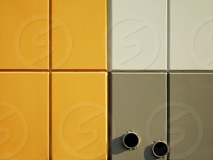 Drain pipes in a colorful wall make an abstract geometric pattern. photo