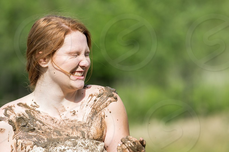 A young woman gets into a mud fight while wearing a bridesmaid dress. photo
