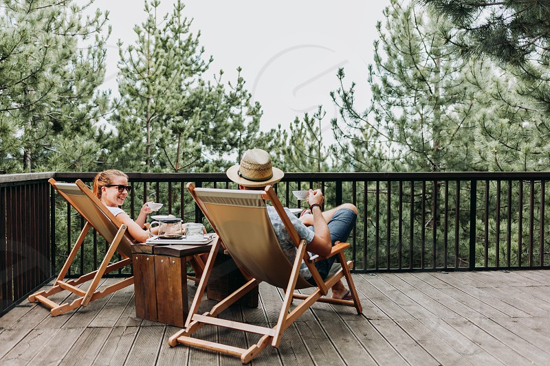Couple enjoying coffee on a balcony in the mountains photo