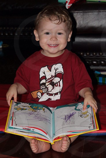 boy in red crew neck t-shirt holding a book photo