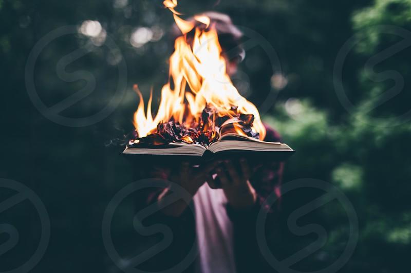 person burning open book selective focus photography photo