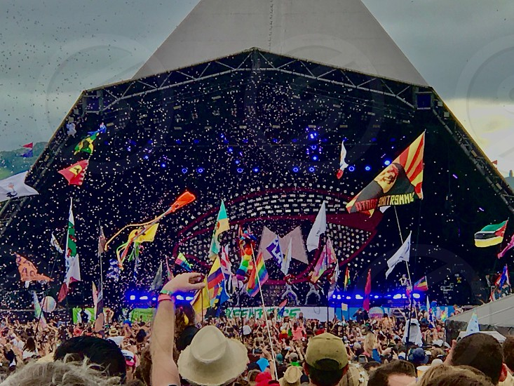 Glastonbury festival music tic a tape flags band excitement lights crowd audience photo