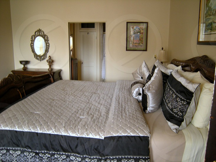 Hotel room with antique mirror and black and white bedspread photo
