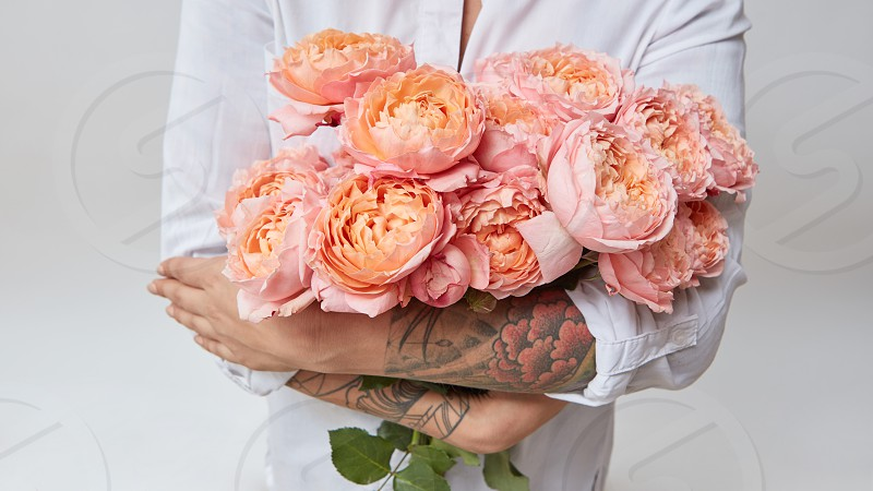 woman with a tattoo on her hands holding a bouquet of pink roses valentine's day photo