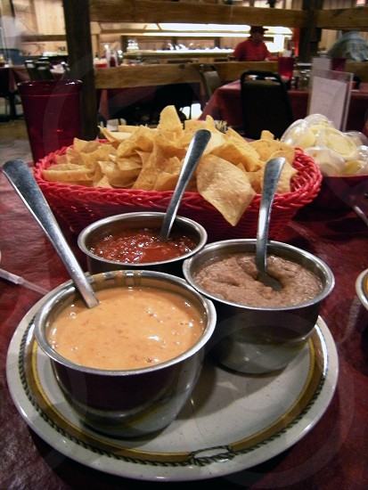 Cheese dip bean dip salsa and chips photo