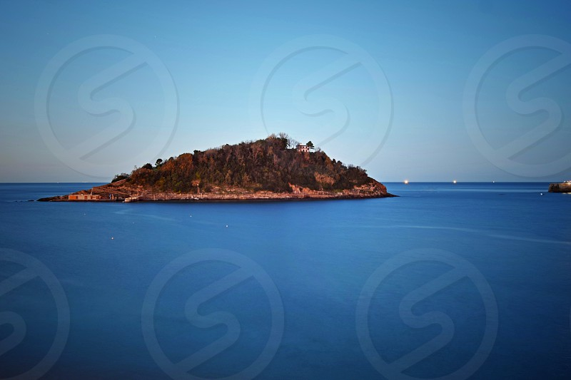 brown islet under blue sky photo