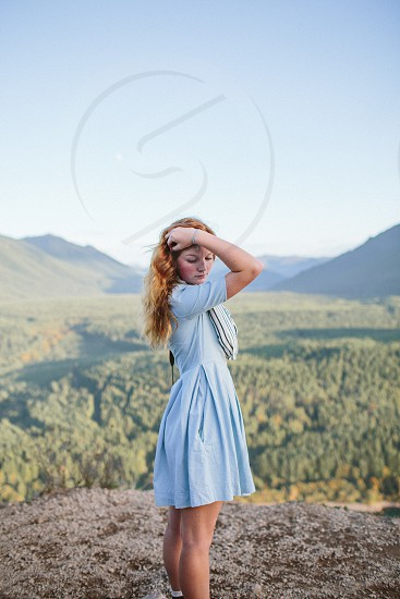 woman in blue dress standing at the cliff photo