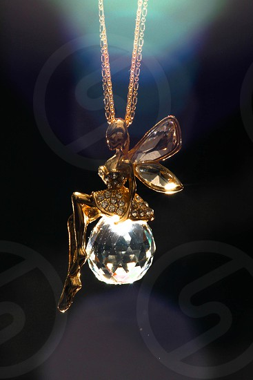 gold fairy sitting on clear crystal ball pendant photo
