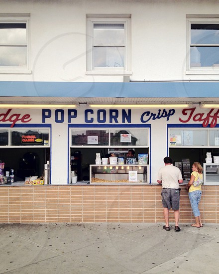 man and woman in front of pop corn crisp store photo