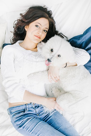 woman in white crew neck sweater hugging white long coat dog while lying on bed photo