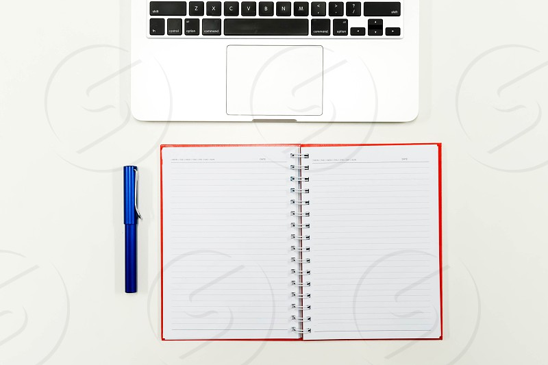 Flat lay photo of white office desk with laptop keyboard pen and notebook top view photo