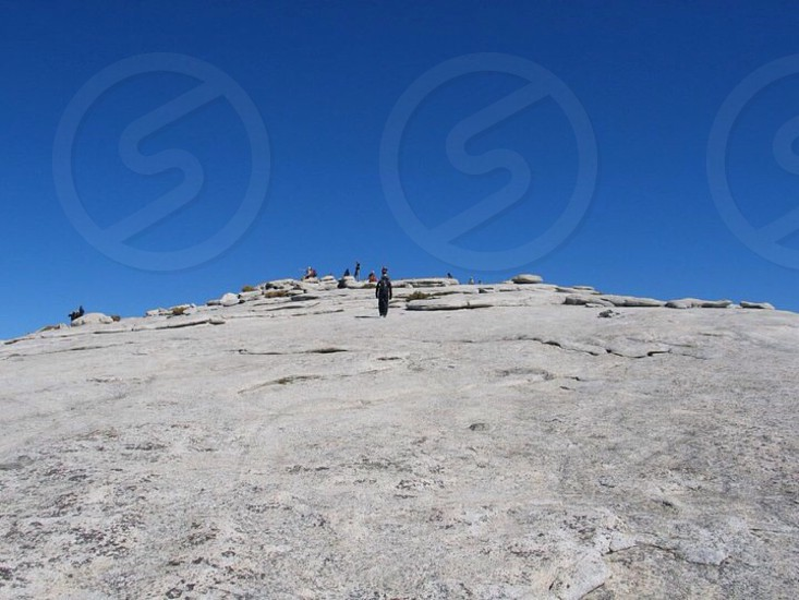 people standing on gray soil on hill top photo