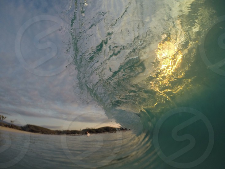 A barrel closing over as the sun sets in the back of the wave.  photo
