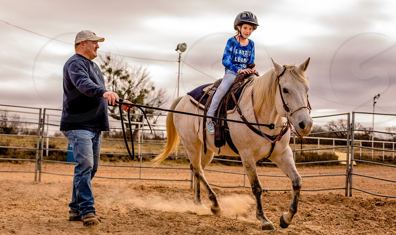 A young girl learning to ride a horse at a ranch in Texas. photo