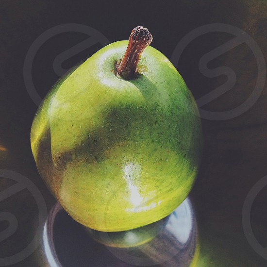 Reflection of a pear in an aluminum bowl photo