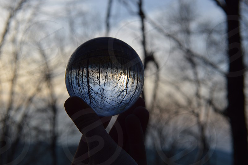 person holding clear glass ball photo