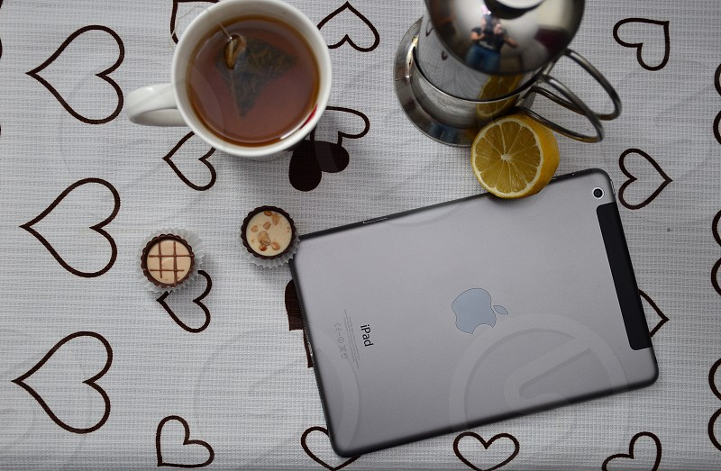 silver ipad beside slice lime stainless steel condiment bottle and white ceramic mug with brown liquid and moth on black and white heart print covered table photo