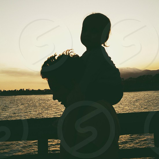 man carrying child silhouette  photo