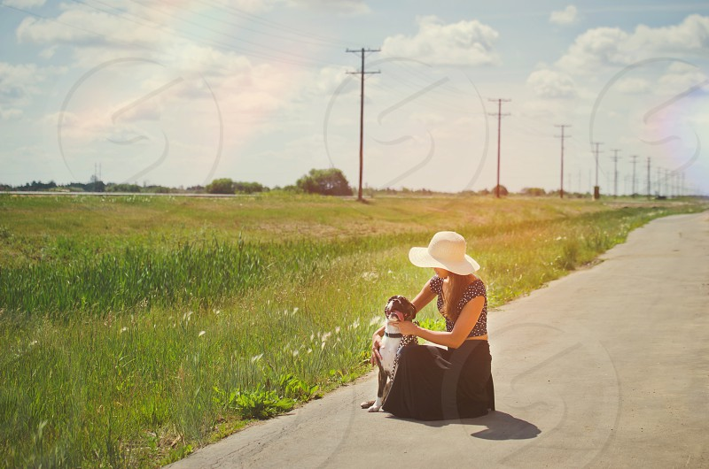 Woman outdoors sitting with dog on a path. Light leak effect. photo